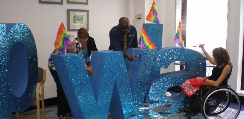 PWDA staff and supporters putting final touches to the Mardi Gras Parade banner