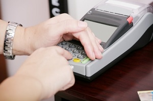 IMAGE: A person enters their pin into machine. With their left hand they shield the keypad.