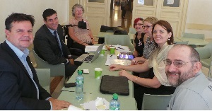 Members of the Australian delegation sit working around a table