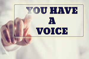 IMAGE: A hand touching a button that has text on it that says 'YOU HAVE A VOICE'.